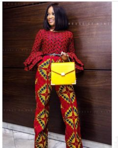 African girl in red ankara jumpsuit with yellow handbag