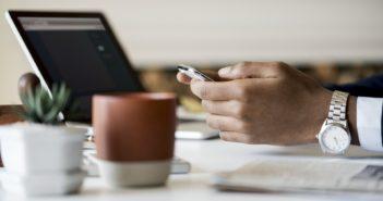 hand with mobile phone, laptop and mug
