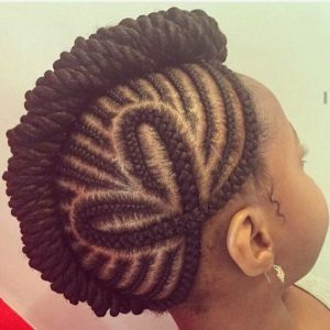Little black girl with tiny cornrow braids forming a mowhawk, and two cornrows forming a heart shape on the side of her head.
