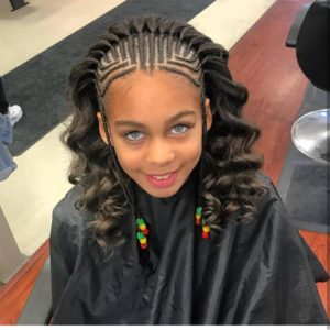 Little girl with precise cornrow braids leading to a cascade of wavy hair from the top of her head