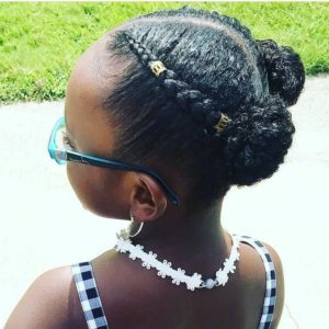 Little black girl with hair plaited in two cornrows, ending in space buns