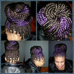 black woman with black and purple box braids swept up in a huge bun